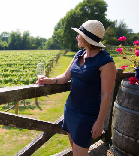 Woman sipping on wine looking out at vineyard