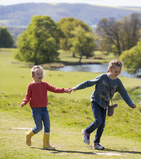 Children holding hands in countryside