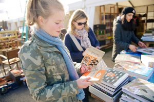 Three ladies looking at books at an antique fair