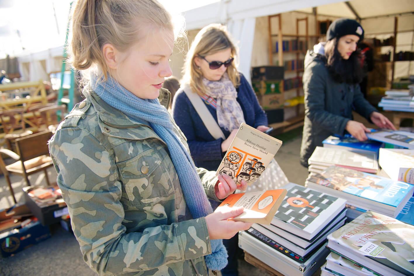 Three ladies looking at books at an antique fair
