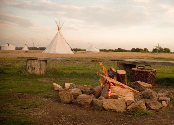 Fire pit with yurts in background in countryside