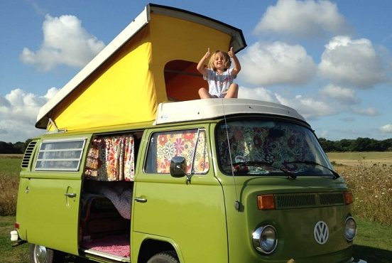 A child with their thumbs up in the camper van