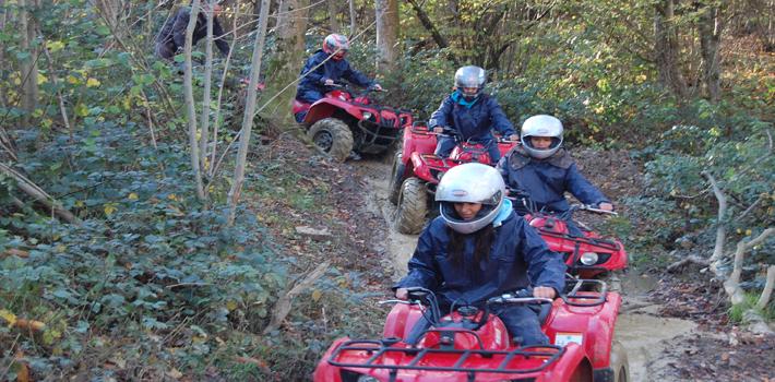 A quad biking group going down a dirt track