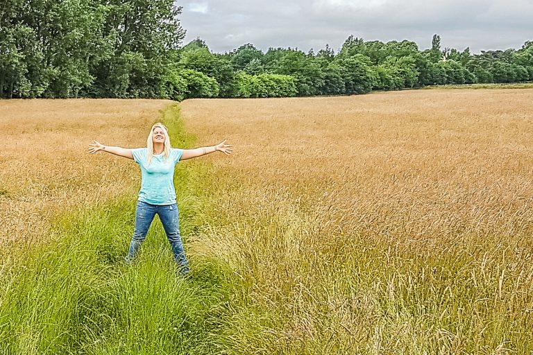 Woman posing with hands out in field