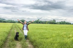 Woman and dog in field