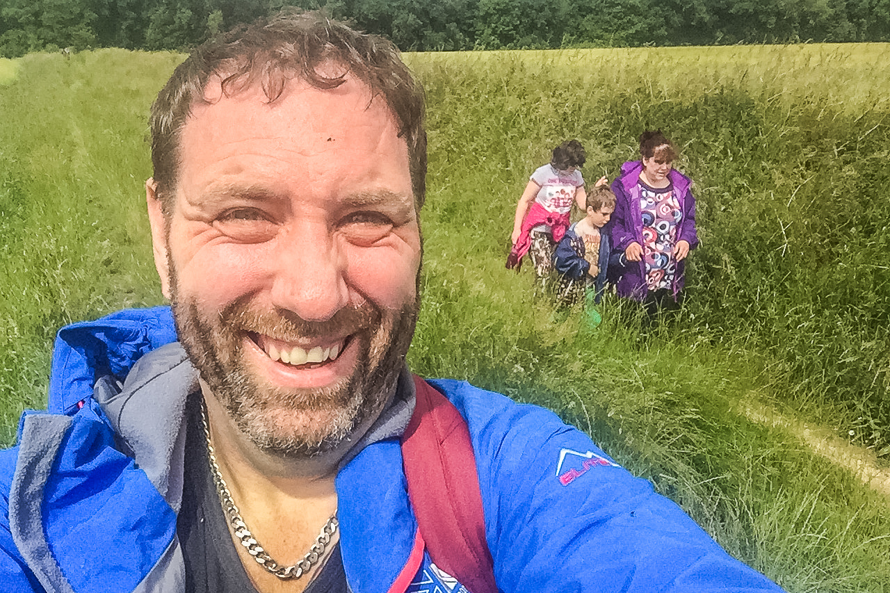 Man taking selfie with family in field