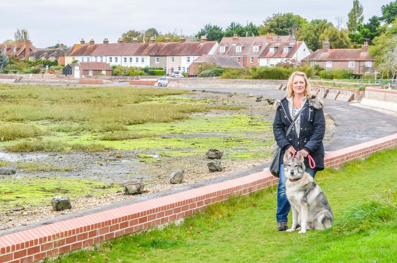 Woman and dog standing by Chichester Harbour