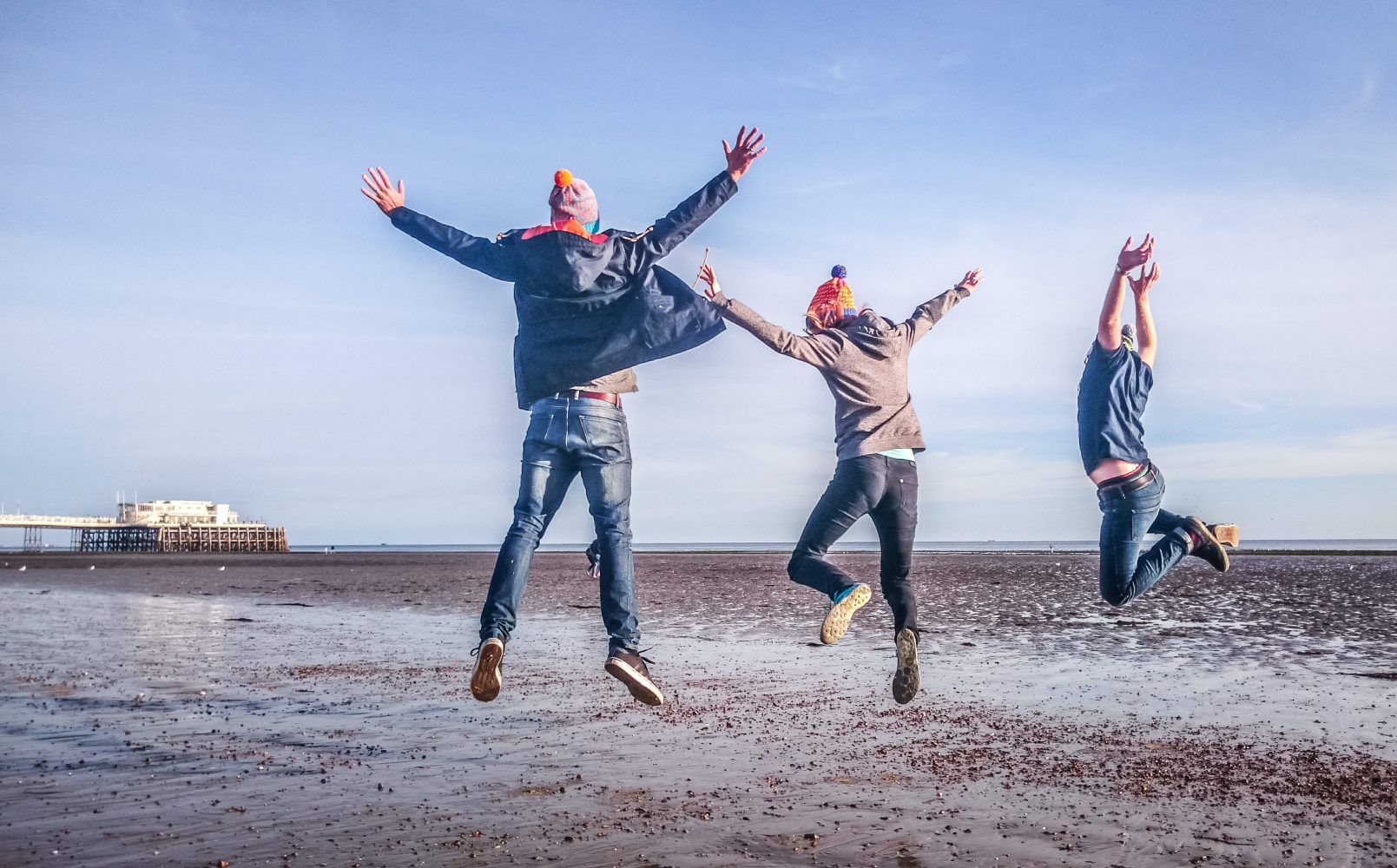 Three people jumping in the air at Worthing beach