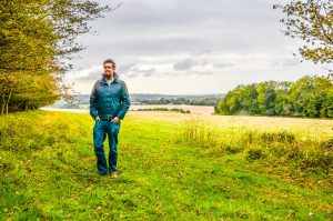 A man posing for a picture in a field