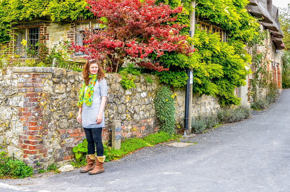 A woman standing in front of a cottage in Amberley