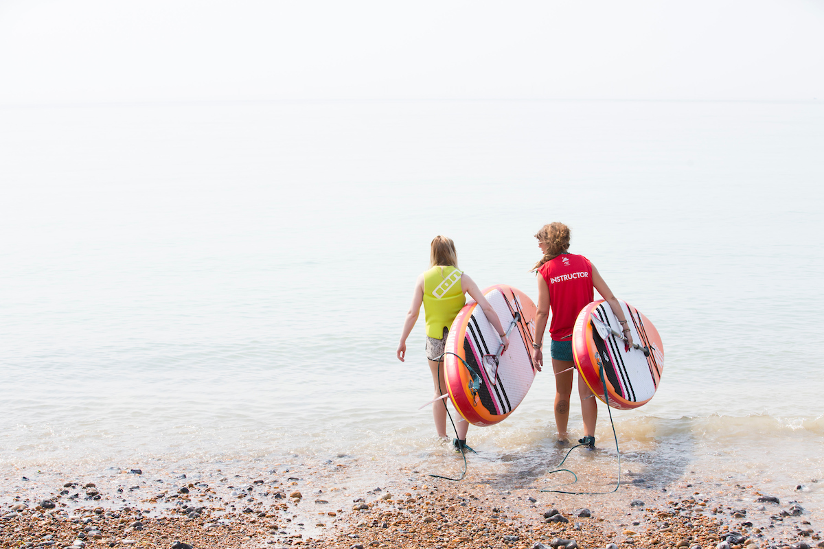 Two surfers walking into the sea