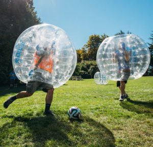 Two people playing bubble football outdoors