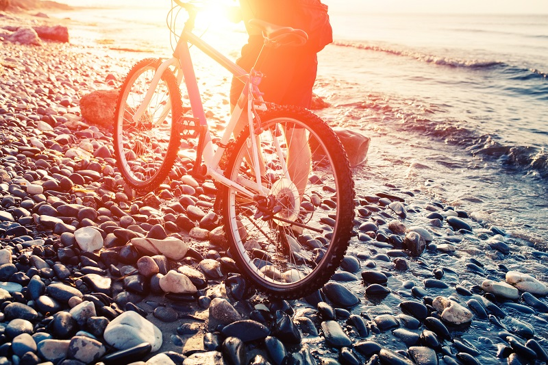 Cyclist walking bike on pebble beach