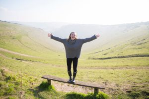 Woman standing on a bench in front of Devils Dyke