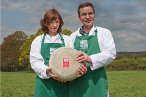 Mark and Sarah owners of High Weald Dairy holding a cheese wheel