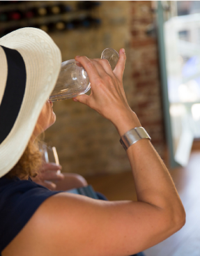 Woman with sun hat wine tasting
