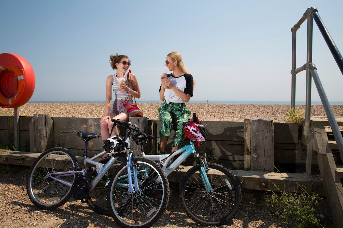 Two female cyclists enjoying a cold drink on Worthing seafront