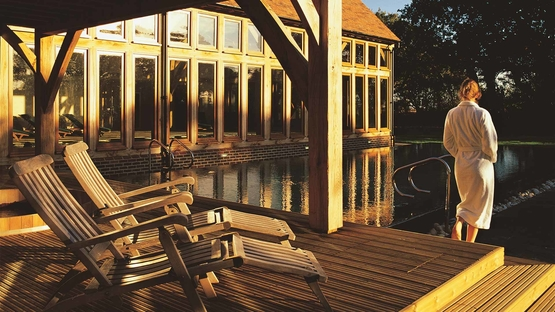Woman in robe at Bailiffscourt Spa in front of the pool at sun rise