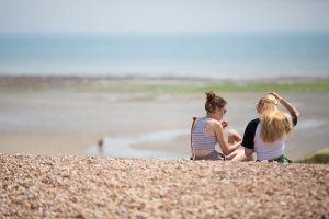 Two girls sitting on Climping Beach