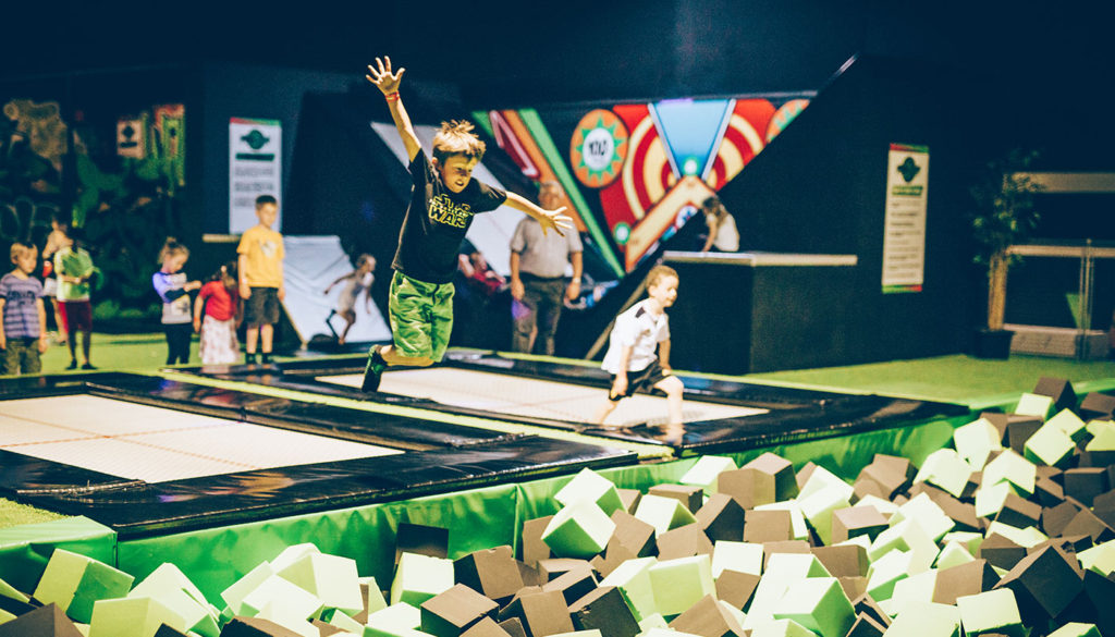 Flip out indoor trampoline park with children jumping into foam pit