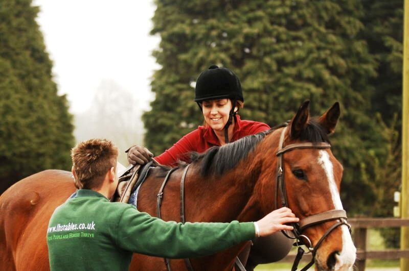 Horse rider and trainer getting on a horse