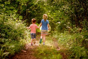 Two children running down a country path on summer holiday in West Sussex