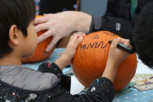 Young boy drawing a face on a pumpkin