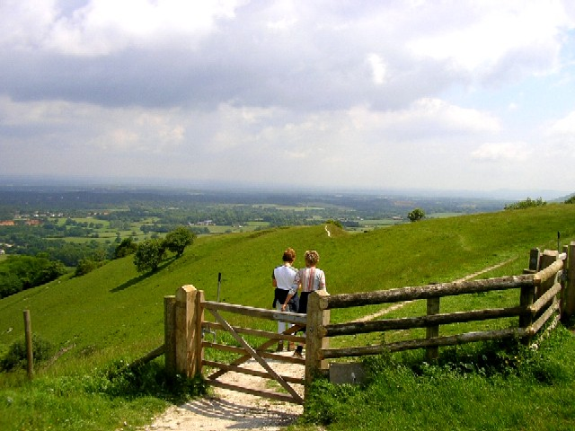 Two people enjoying a walk in the green countryside in Sussex