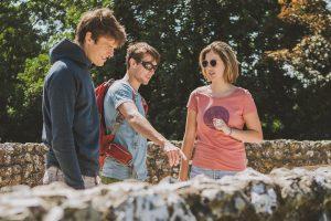 Three friends looking at a flint wall