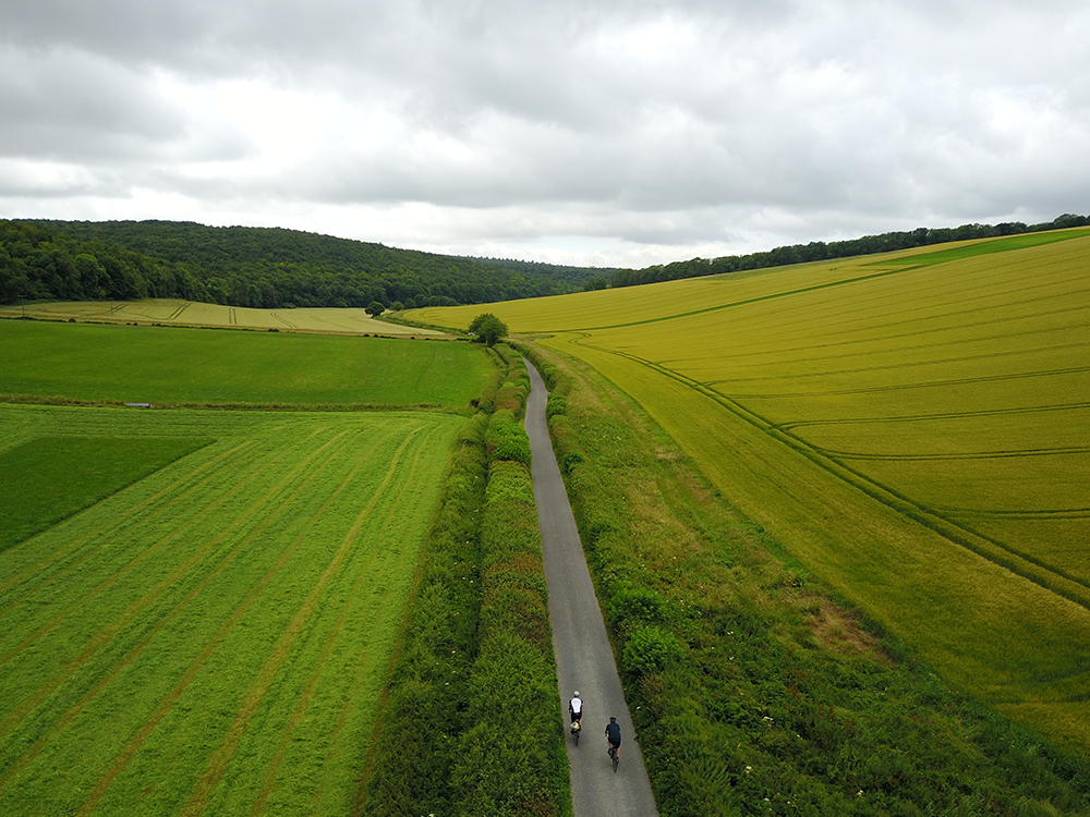 Two cyclists riding through lush green countryside in West Sussex