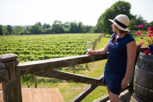 A woman in a hat looking out over the vineyard and tasting wine at Nutbourne Vineyard