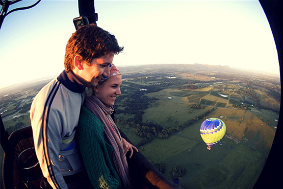A couple in a hot air balloon looking down at the countryside in Susex