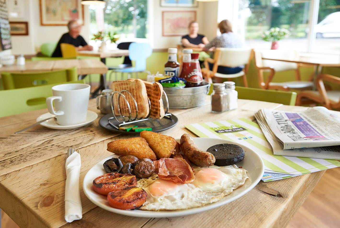 Billy's on the road English fry up on a table with newspaper and coffee