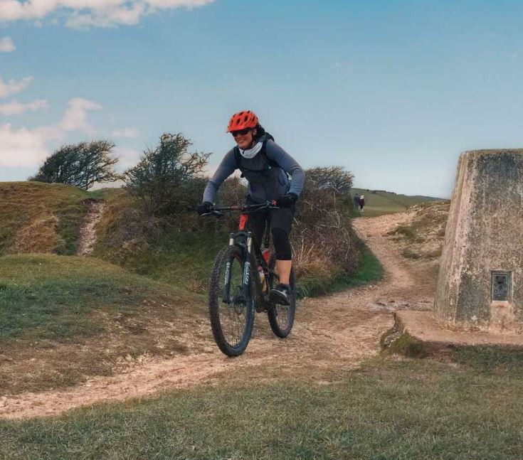 Woman cycling through a bike trail in South Downs
