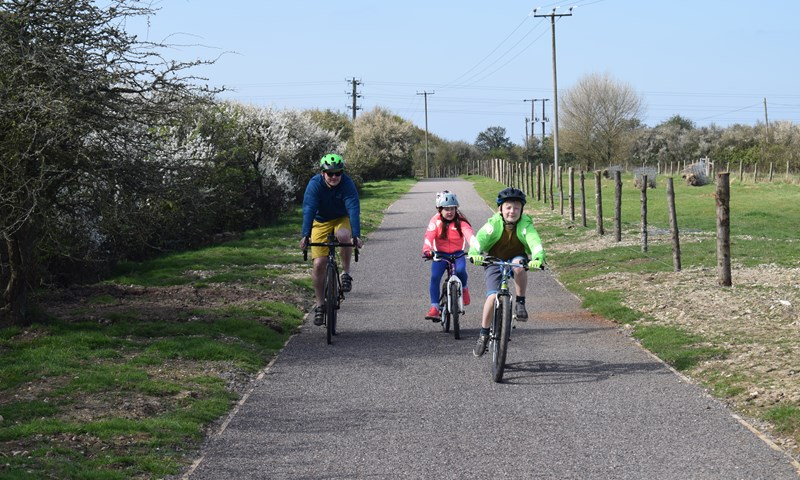 A family cycling on a path from Pagham to Medmerry