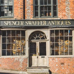 Historic red brick frontage of Spencer Swaffer Antisues shop with wooden double doors and mirrors in the window