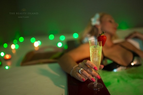 Woman relaxing in a hot tub with champagne at The Beauty Island Sanctuary