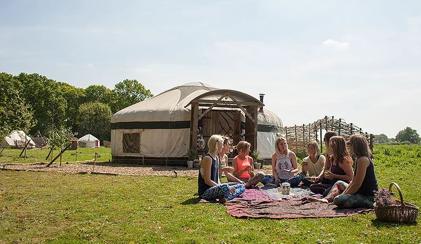 A group of ladies having a picnic outside a yurt
