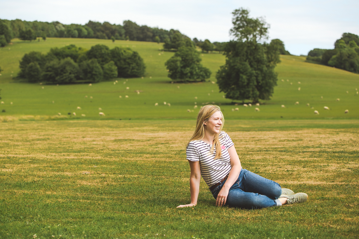 Woman sitting on grass in the West Sussex countryside