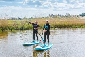 A couple river paddleboarding on the River Arun with Arundel castle in the background