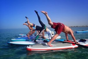 Brighton Kitesurf SUP Academy teaching SUP yoga to a group on the water