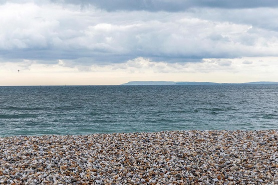 Shoreham beach pebbles and sea with headland in the background