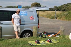 Owner of Learn to kitesurf next to his van waiting for a lesson in Sussex