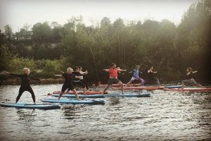 A group of people trying out SUP yoga on a river in Sussex