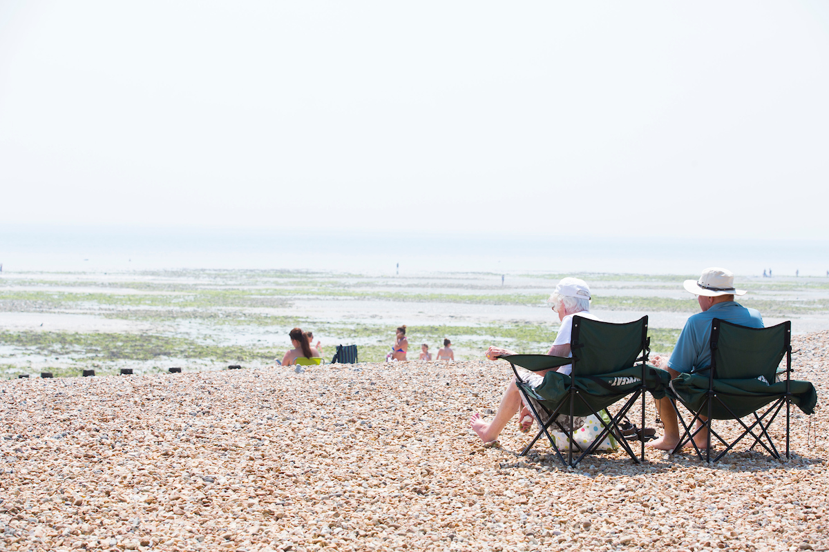 An older couple on camping chairs enjoying the beach scenery