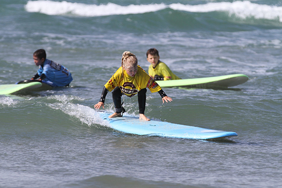 Small girl learning to stand on a surfboard on a family surfing lesson in West Sussex