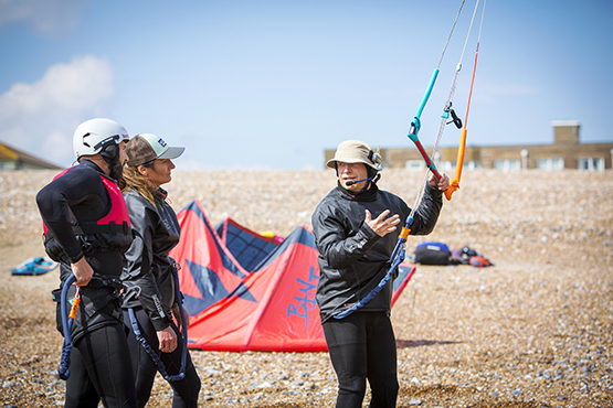 A couple learning to kitesurf with an instructor on Lancing beach
