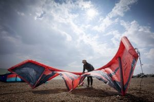 Man on Lancing beach preparing the kite for a kite surfing session with BN1 Kitesurfing