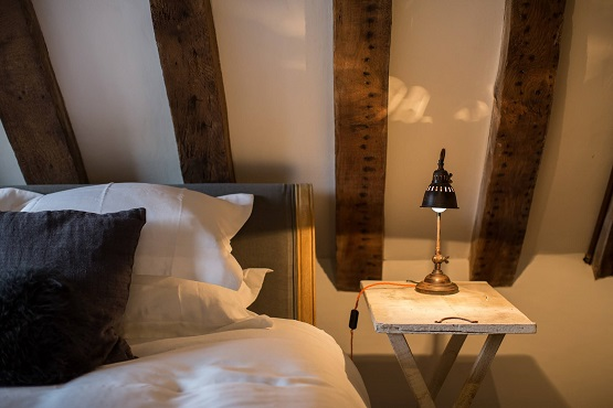 Comfy bed, side table and lamp at one of th Cabins and Castles properties