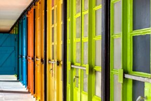 Brightly coloured beach hut doors of The East Beach Studios in Worthing
